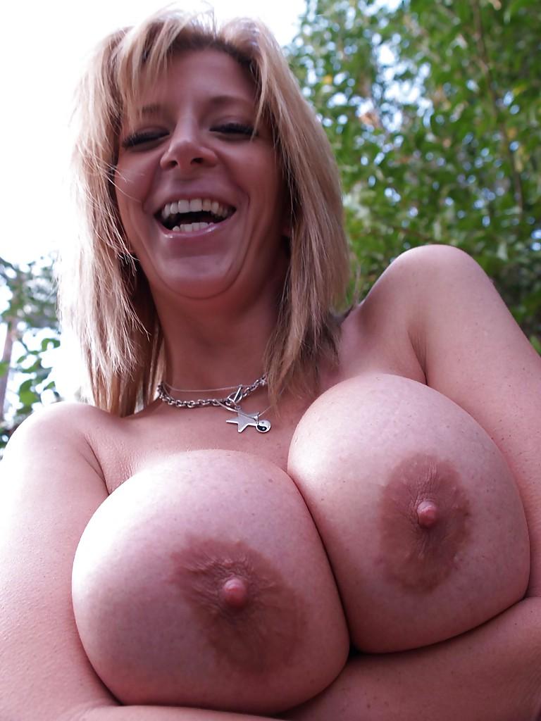 Sara Jay поддерживает руками большую грудь во время фотосессии