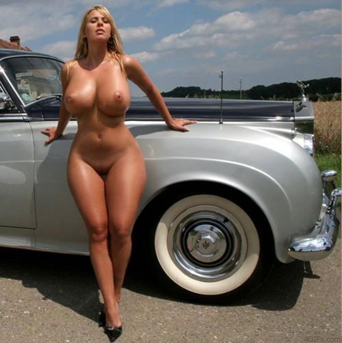Белокурая девица с огромными сиськами оперлась на дорогую машину