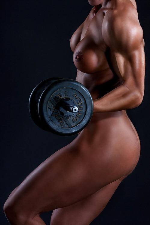 Мускулистая девушка совсем голая поднимает гантели