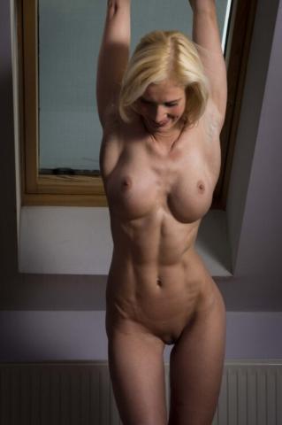 Мускулистая девушка показывает всю красоту своего обнаженного тела