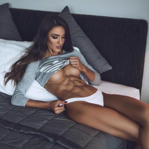 Загорелая красавица с мускулистым телом раздевается на кровати